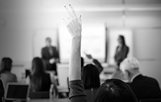 A lady raising her hand in a classroom setting