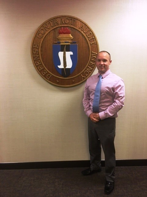 Shawn standing next to the Defense Contract Audit Agency seal.
